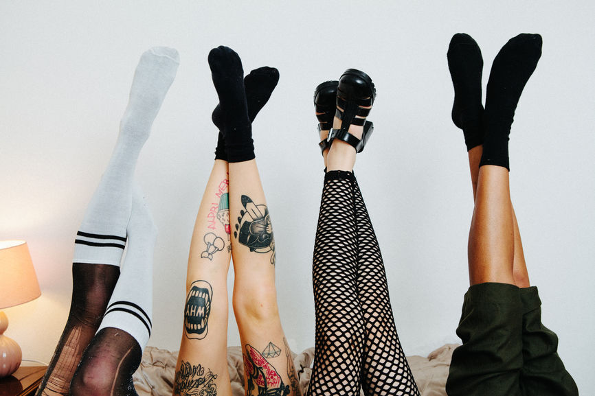 Four sets of legs raised in the air showing four different styles of dress, from long socks and tights, to fishnets, and trousers.